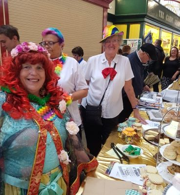 The Plazarettes raising donations with theirmagnificent home made cake stall - Stockport Pride