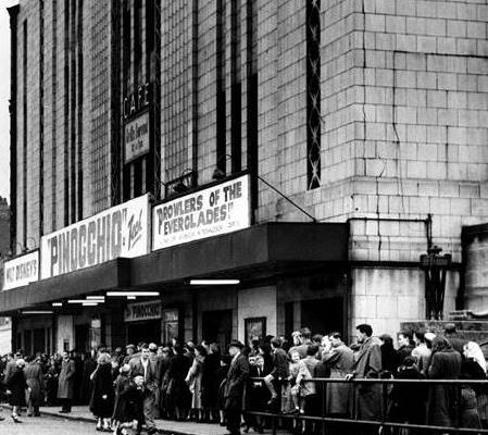Queue's forming for what is believed to be the 1953 screening of Pinocchio due to the screening of 'Prowlers of The Everglades' advertised on the canopy boards